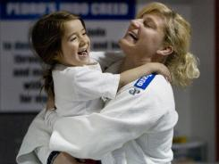 """Kayla Harrison, right, hugs Taila Pedro, 4, the daughter of her coach, Jimmy Pedro, following a workout in May. """"It's ridiculous how lucky I got,"""" Harrison said of getting the opportunity to be coached by Pedro."""