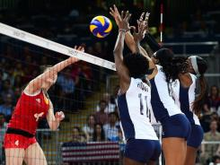 China's Ruoqi Hui gets her shot blocked by the USA's Megan Hodge (11), Foluke Akinradewo (16) and Destinee Hooker (19) during Wednesday's preliminary game.