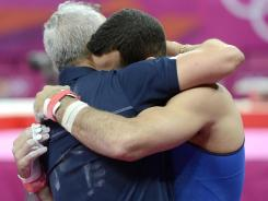 Danell Leyva, in blue, hugs coach and step-father Yin Alvarez after competing on the high bar in the men's all-around final and clinching the bronze medal.