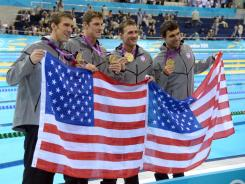 U.S. team members, from left, Michael Phelps, Conor Dwyer, Ryan Lochte and Ricky Berens pose with their gold medals and American flags after winning the men's 4x200-meter freestyle relay final.