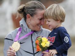 Kristin Armstrong of the USA celebrates her victory in the individual time trial Wednesday with her medal and son Lucas.