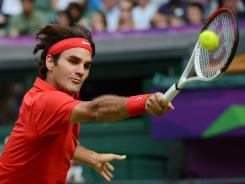 Roger Federer of Switzerland reaches for a backhand during his victory Thursday against John Isner of theUSA.