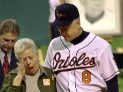 Cal Ripken escorts his mother, Vi, from the field on Oct.6, 2001, after she threw out the ceremonial first pitch before his final game, at Oriole Park in Baltimore. Last month she was abducted at gunpoint but was found unharmed.