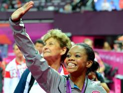 Gabby Douglas waves to the crowd after receiving her gold medal for winning the women's individual all-around final in the London Olympics.