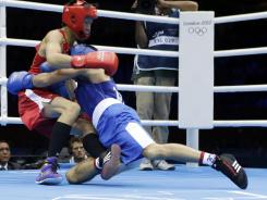 Japan's Satoshi Shimizu, left, knocked Azerbaijan's Magomed Abdulhamidov down six times in the third round of their bantamweight match Wednesday. The referee did not count any of the six as knockdowns.