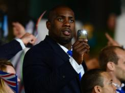 Teddy Riner, who won bronze at the 2008 Beijing Olympics, marches with the French delegation during the opening ceremony July 27.