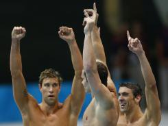 Michael Phelps, right, Brendan Hansen, center, and Matthew Grevers, left, celebrate as teammate Nathan Adrian swims the anchor leg in the 4x100-meter medley relay finals, securing the gold medal for the USA in Phelps' final career Olympic event Saturday.