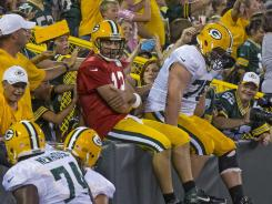 Packers quarterback Aaron Rodgers (12) and offensive tackle Bryan Bulaga (75) do a Lambeau Leap after a touchdown during Friday night's scrimmage.
