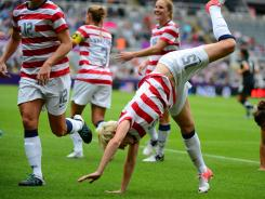U.S. players including Megan Rapinoe (15) do cartwheels to celebrate a goal by forward Abby Wambach (not pcitured) in the first half of a women's soccer Olympic quarterfinal match Friday.