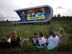 Visitors watch a broadcast of Olympic competitions on a big screen television at the Olympic Park.