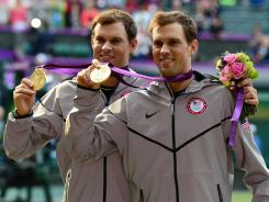 Mike Bryan, left, and Bob Bryan show off their gold medals after winning the men's doubles final Saturday.
