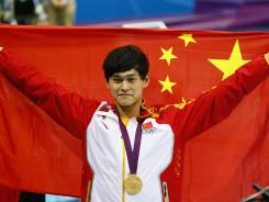 Yang Sun celebrates with his flag after setting a world record at 14:31.02 and winning the gold medal in the men's 1,5000-meter freestyle final in the London Olympics on Saturday.