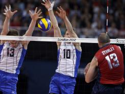 Russia's Dmitriy Muserskiy, left, and Yury Berezhko, center, block a spike by the USA's Clayton Stanley during Saturday's match.