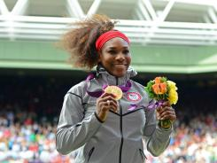 "Serena Williams holds up the gold medal as she celebrates after her ""golden slam"" win at London 2012."