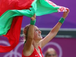 Victoria Azarenka raises the flag of Belarus after defeating Maria Kirilenko of Russia to win the bronze medal in women's singles.