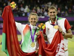 Victoria Azarenka, left, and Max Mirnyi hold the flag of Belarus and their gold medals after winning the mixed doubles final at Wimbledon.