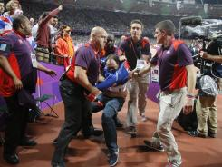 A spectator is detained by security after a beer bottle was thrown on to the track during the start of the men's 100-meter final, on Day 9 of the London 2012 Olympic Games at the Olympic Stadium in London, England.