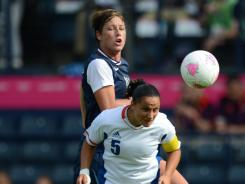 USA forward Abby Wambach and France forward Ophelie Meilleroux (5) jump to head a ball in the women's preliminary match before the London Olympics.