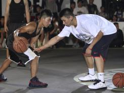 Houston Rockets guard Jeremy Lin, right, holds a basketball clinic with young Taiwanese players in Taipei on his first visit to the country of his parents' birth.