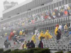 Fans leave the stands after it rained Sunday at Pocono Raceway.