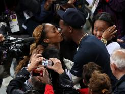 Sanya Richards-Ross of the United States kisses her husband, NFL cornerback Aaron Ross, after winning gold in the women's 400 meters.