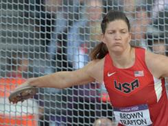 Stephanie Brown Trafton throws a discus that will be retrieved by a Mini MINI.
