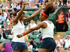 Venus and Serena Williams celebrate their third Olympics doubles gold medal.