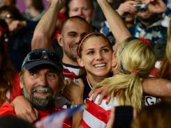 U.S. forward Alex Morgan celebrates with teammates after scoring the winning goal in extra time against Canada in the semifinals Monday at Old Trafford in Manchester, England.