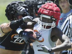 Hoover's Taylor Brown grabs for Evangel's Isaiah Johnson in the National Select 7 on 7 championship game at Hoover, Ala., on July 28. Both teams wore the Guardian helmet covers in the game.