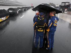 NASCAR crew members stand in the pits in a downpour that shortened Sunday's Sprint Cup race at Pocono, where a fan was killed by lightning.