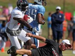In what many were describing as the best hit of the day, Falcons wide receiver Drew Davis, left, levels his head coach, Mike Smith, after catching a pass during a combined practice with the Titans on Monday.