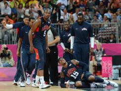 U.S. players react as Carmelo Anthony rolls on the ground after being knocked in the groin by Argentina's Facundo Campazzo at the end of the third.