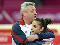 Aly Raisman hugs coach Mihai Brestyan on Tuesday after competing in the floor exercise, which she won.