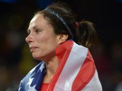 Jenn Suhr takes a tearful victory lap with the U.S. flag after winning women's pole vault.