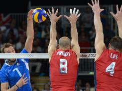 Italy's Michal Lasko, left, spikes as U.S. player William Priddy, center, and David Lee attempt to block during the men's quarterfinal volleyball match between the U.S. and Italy at the 2012 London Olympic Games in London.