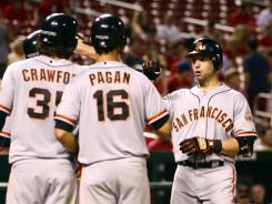 Giants third baseman Marco Scutaro is congratulated after hitting a grand slam against the Cardinals on Wednesday night.