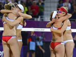 Kerri Walsh, far left, hugs Jennifer Kessy, and Misty May-Treanor hugs April Ross, far right, after an all American gold medal match in women's beach volleyball.