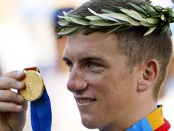 In this Aug. 18, 2004, file photo, Tyler Hamilton holds up his gold medal after the men's road individual time trial in the 2004 Olympic Games in Athens.