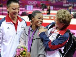 "Gabby Douglas, with coach Liang Chow, left, and team coordinator Marta Karolyi, is the first African American to win the gymnastics all-around gold. ""She's going to have a huge influence"" on aspiring Olympians, former gymnast Dominique Dawes said."
