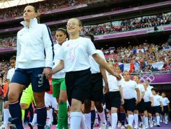 U.S. defender Christie Rampone (3) leads youngsters and her teammates onto the field before the women's soccer gold medal match against Japan on Thursday.