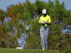 Tiger Woods looks over his notes Thursday during the first round of the PGA Championship at Kiawah Island, S.C., where the paspalum grass on the fairways and greens is a rare surface on tour for the golfers.