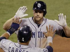 The Padres' Chase Headley, top, celebrates with teammate Everth Cabrera after hitting a two-run homer off Pirates pitcher Tony Watson in the seventh inning.