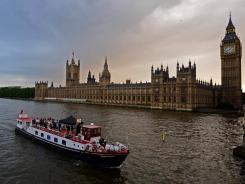 London, United Kingdom; A passenger boat passes in front of Big Ben on the Thames River.
