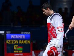 Steven Lopez of the USA leaves the mat after losing his opening match to Ramin Azizov in taekwondo.