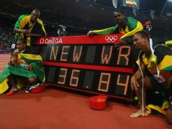 Usain Bolt, Yohan Blake, Michael Frater and Nesta Carter of Jamaica celebrate next to the clock after winning gold and setting a new world record in the men's 4x100 relay.