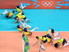 Brazil players celebrate by doing front flips on the court following their victory against the USA in the women's volleyball gold medal game. Brazil won their second consecutive gold.