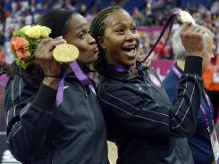 Tamika Catchings, right, and teammate Swin Cash celebrate after the USA defeated France for the women's basketball gold medal.
