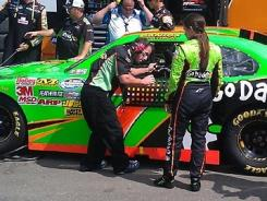 Danica Patrick waits outside her No. 7 Chevrolet with hopes of returning to the track Saturday. But the car sustained too much damage and was retired after completing two laps.
