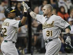 The Athletics' Jonny Gomes, right, celebrates with Yoenis Cespedes after hitting a solo home run against the White Sox during the eighth inning.
