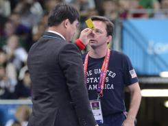 Referee Tong Kun Chung, left, issues a yellow card to U.S. coach Zeke Jones after he disputed a call during the match between Jake Herbert and Sharif Sharifov.